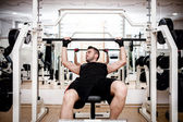 Man working out at gym, chest bench press exercise — Stock Photo