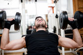 Bodybuilder training in the gym: chest - dumbbell bench press — Stock Photo