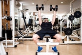 Young man training at gym with dumbbell, chest bench exercise — Stock Photo