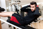 Handsome muscular man doing sit-ups on a incline bench at fitness center and gym — Stock Photo