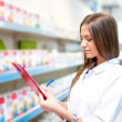 Beautiful blonde pharmacist in drugstore or pharmacy taking notes. Portrait of health care doctor in pharmacy writing on clipboard — Foto de Stock