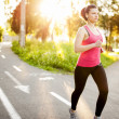 Atheletic fitness woman jogging outdoors in city park at sunset — Stock Photo