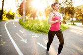 Atheletic fitness kvinna jogga utomhus i stadsparken vid solnedgången — Stockfoto