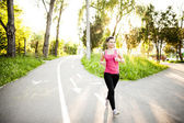 Portrait of a smiling active female runner. Fitness female jogger in urban life — Stock Photo
