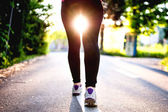 Close-up of female feet, legs and shoes while running in city park. Urban fitness concept with female athlete running — Stock Photo