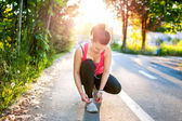 Portrait of active joggin woman resting and preparing shoes for training in park at sunset — Stock Photo