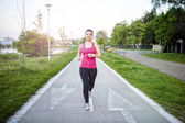 Beautiful running girl, jogging and preparing for marathon. Fitness girl running in park on special track at sunset — Stock Photo