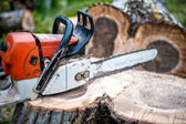 Gasoline powered professional chainsaw on pile of cut wood, timber wood — Stock Photo