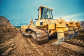 Close-up of bulldozer or excavator working with soil on highway  — Stock Photo