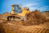 Excavator working with earth and sand in sandpit in highway construction site — Stock Photo