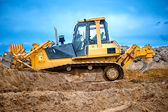 Bulldozer or excavator working with soil on construction site of building, road or industrial hall — Stock Photo