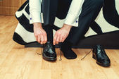 Groom wearing shoes on wedding day, tying the laces and preparing. Business man dressing up with classic, elegant shoes — Stock Photo