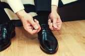Business man dressing up with classic, elegant shoes. Groom wearing shoes on wedding day, tying the laces and preparing. Vintage effect — Stock Photo