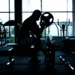 Silhouette of an athletic man working out at gym. Fitness bodybuilder training in the gym — Stock Photo #49629781