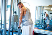 Athletic fitness coach, bodybuilder training at gym, triceps exercises — Stock Photo
