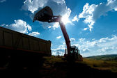 Industrial excavator loading earth into a dumper truck at construction site — Stock Photo