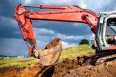 Eathmover, industrial digger and excavator working in sandpit on construction site — Stock Photo