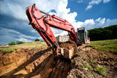 Excavator loading dumper truck tipper in sandpit in highway construction site and quarry — Stock Photo