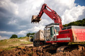 Heavy bulldozer and excavator loading and moving red sand or soil on road construction site or quarry — Stock Photo