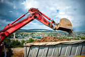 Close-up of industrial excavator loading a dumper truck with soil and earth from construction site — Stock Photo
