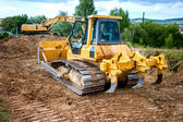 Industrial backhoe truck moving earth and soil in quarry construction site — Stock Photo
