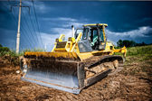 Industrial backhoe, bulldozer moving earh and sand in sandpit or quarry — Stock Photo