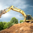 Backhoe and industrial excavator working in construction site, quarry and loading earth in dumper truck — Stock Photo #49925463