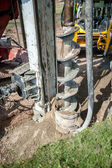 Close up of construction auger, industrial drilling rig making a hole in the ground — Stock Photo