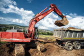 Industrial excavator loading soil material from highway construction site in a dumper truck — Stock Photo