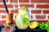 Jug of fresh summer mind lemonade with ingredients on wooden tab — Stock Photo