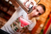 Barman preparing and pouring cosmopolitan alcoholic cocktail drink at bar. Alcoholic drink with vodka, triple sec, cranberry juice and lemon juice — Stock Photo