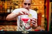 Barman preparing cosmopolitan alcoholic cocktail drink at bar. Alcoholic drink with vodka, triple sec, cranberry juice and lemon juice — Stock Photo