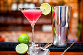 Cosmopolitan cocktail drink at casino and bar served with lime and ice — Stock Photo