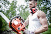 Portrait of angry muscular male lumberjack, woodworker with chainsaw in hand, posing — Stock Photo