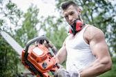 Portrét agresivní svalnatý muž dřevorubec, architekt s motorovou pilou v ruce, představuje — Stock fotografie