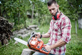 Portrait of sexy and handsome man with chainsaw and protective gear ready for cutting wood — Stock Photo