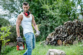 Portrait of expressive muscular lumberjack, man with chainsaw and tank top in forest — Stock Photo