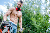 Portrait of aggressive athletic man with chainsaw getting ready for fire wood cutting — Stock Photo