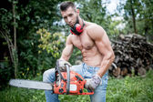 Portrait of handsome athletic man with chainsaw and protective gear ready for cutting wood — Stock Photo