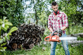 Portrait of aggressive, muscular and athletic man with chainsaw getting ready for fire wood cutting — Stock Photo
