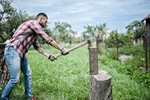 Athletic man splitting wood and cutting firewood with axe  — Stock Photo