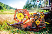 Detail of harvester machinery, tractor at farm with combine collecting mature grain crops — Stock Photo