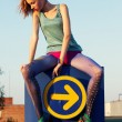 Pretty slim woman sitting on road indicator — Stockfoto