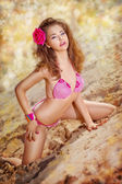 Pretty young voluptuous girl in pink bikini with red flower — Stock Photo