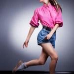 Fashion girl in denim shorts running in studio - glamor style — Stock Photo #13284553