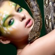 Stock Photo: Beautiful young woman with a snake (python) - circus performance