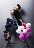 Pretty cheerful fashion retro teen girl laughing on ladder — Stock Photo