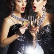 Two beautiful women with champagne singing christmas songs — Stock Photo