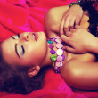 Dreamy sensual romantic girl in red dress lying in bed — ストック写真