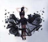 Balançoire. femme sensuelle en noir flottant robe papillons — Photo